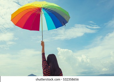 Young woman holding colorful umbrella on the beach in summer . Summer Vacation Concept. Filtered image processed vintage effect.