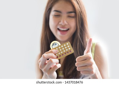 Young woman holding condom and contraceptive pills prevent pregnancy