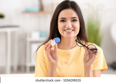 Young woman holding contact lens case and glasses on blurred background