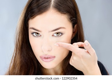 Young woman holding contact lens on finger in front of her eye