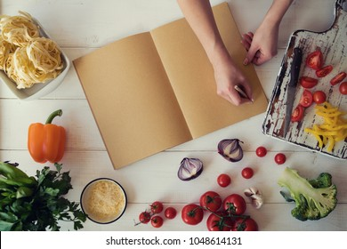 Young woman is holding cookbook and writing a new recipe. Female chef with cookbook. Cooking, culinary, food and people concept. Fresh organic vegetables and spices on a wooden background. Heatly food