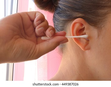 Young woman holding a cotton swab to clean the ear and clean it. Hygiene of the body.