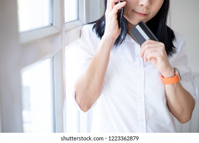 Young woman holding credit card and using smartphone. Online shopping concept