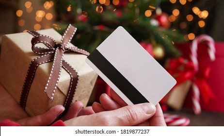 Young woman holding a credit card and a gift box against the background of Christmas decor and gifts, close-up. Christmas and New Year shopping on the Internet, payment by credit card.