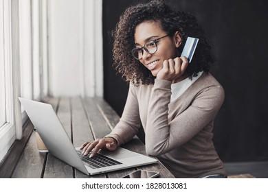 Junge Frau mit Kreditkarte und Laptop