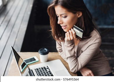 Young woman holding credit card and using laptop computer. Businesswoman or entrepreneur working at home. Online shopping, e-commerce, internet banking, spending money, working from home concept
