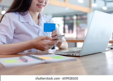 Young woman holding credit card and using mobile smartphone laptop computer. Online shopping concept