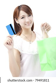 young woman holding credit card and shopping bag