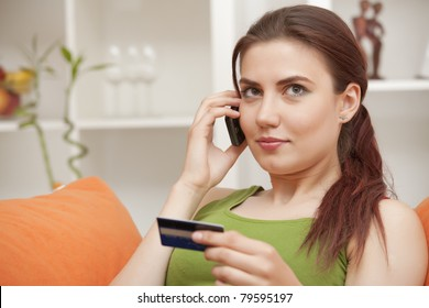 young woman holding credit card and making purchase on cell phone