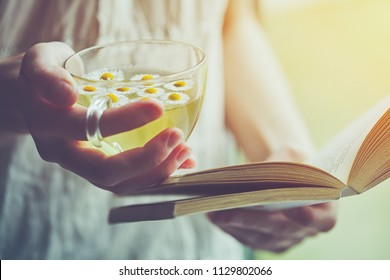 young woman holding cup of chamomile tea and reading open book