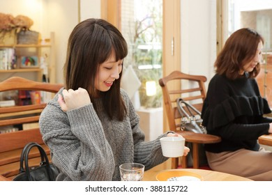 Young woman holding cup of coffee in cafe
