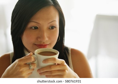 Young woman, holding cup of coffee, looking away