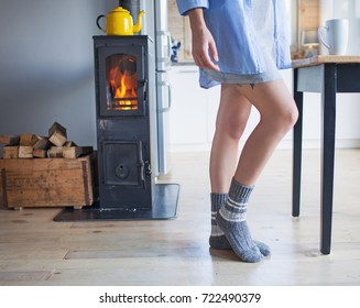 Young woman holding cup of coffee standing by the fireplace. Wooden cabin interior.