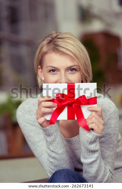 Young woman holding a decorative gift tied with a large red bow in front of her face in a Valentines Day, Christmas or birthday concept for a sweetheart or loved one