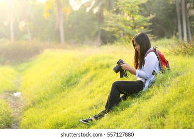 Young woman holding a digital camera, checking a picture result, carrying a backpacker, sitting on a grass or lawn - Traveller concept