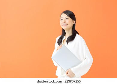 young woman holding digital tablet against orange background