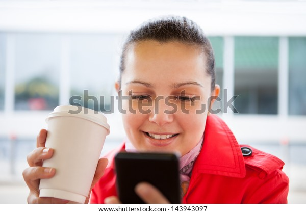 Young woman holding disposable cup and using cell phone in restaurant