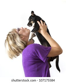 Young woman holding dog above head