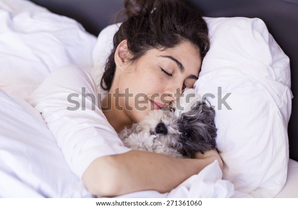 young woman  is holding a dog while laying on a bed. Horizontal shot.