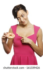 Young woman holding a doughnut looking guilty