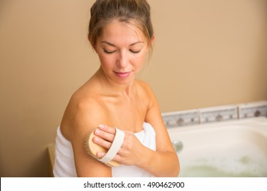 Young woman holding dry brush to side of her shoulder