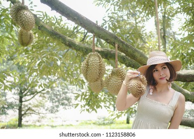 young woman holding durian fruit, Thailand traditional fruit.