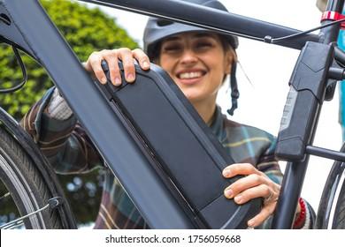 junge Frau, die eine auf Rahmen montierte elektrische Bikebatterie hält