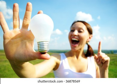 Young woman holding  electric bulb in hand.