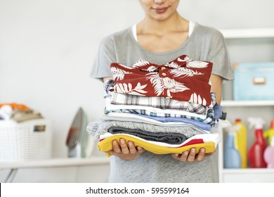 Young woman holding folded laundry