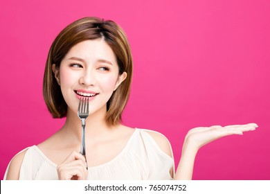 young woman holding fork and showing tasty food