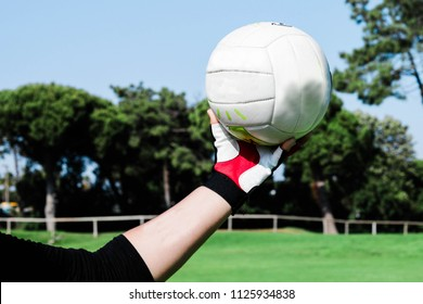 Young woman holding a gaelic football with gloves during gaelic training on a football pitch outdoors