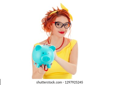 Young woman holding giving proposing a piggy bank to you looking at camera with cheerful expression on face. Caucasian person in yellow dress and coral necklace with red lipstick redhead hair on white