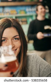 Young woman holding glass of beer with waiter in background