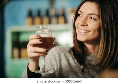 Young woman holding glass of beer in a pub