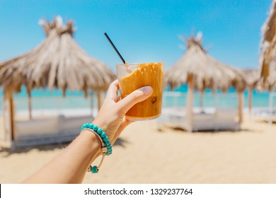 Young woman holding glass of iced coffee at the beach with blue clear water. Greek frappe drink in hands, enjoying sea view