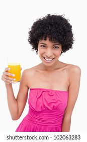 Young woman holding a glass of orange juice while smiling