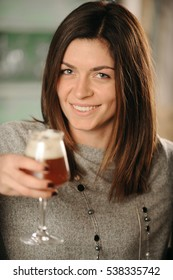 Young woman holding glass of red beer