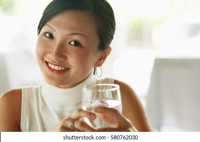 Young woman holding glass of water, portrait