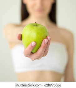 Young woman holding green apple in hand. Girl with green apple in hand on white background
