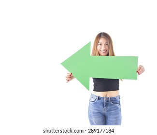 Young woman holding a green arrow pointing to a side against a white background