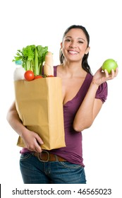 Young woman holding a grocery bag and showing a fresh apple isolated on white background