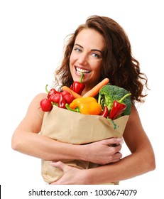 Young woman holding grocery paper shopping bag full of fresh vegetables. Diet healthy eating concept isolated on a white background