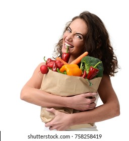 Young woman holding grocery paper shopping bag full of fresh vegetables. Diet healthy eating concept.