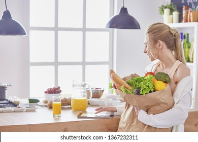 Young woman holding grocery shopping bag with vegetables Standi