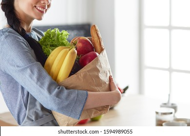 Young woman holding grocery shopping bag with vegetables .Standing in the kitchen