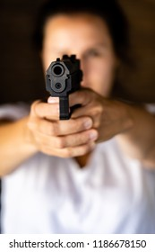 Young woman holding a gun and aiming toward a camera. Pistol in hand and pointing.