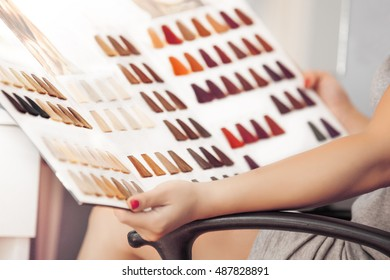 Young woman holding hair color swatches.