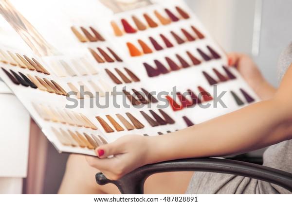 髪の色見本を持つ若い女性。