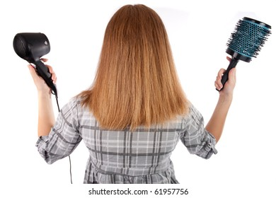 Young woman holding a hairdryer and a brush,isolated on white