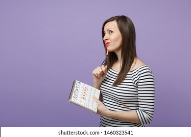 Young woman holding in hand female periods calendar for checking menstruation days isolated on violet purple background studio portrait. Medical healthcare gynecological concept. Mock up copy space